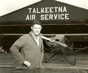 Don Sheldon poses with his Super Cub in front of the Talkeetna Air Service hangar