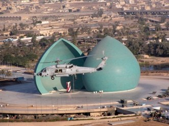 A Helicopter from HCS-5 transits over downtown Baghdad during the early phase of OIF.