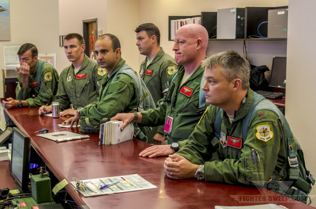 """Cheetah,"" ""T-Bone,"" ""Glover,"" and other pilots from the 64 AGRS get their step brief before walking out to their jets for a training mission at Nellis AFB, Nevada."