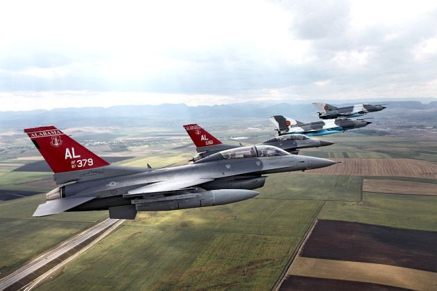 """Two """"Red Tail"""" F-16Cs from the 100 FS of the Alabama Air National Guard's 187 FW fly in formation with two Romanian MiG-21 LanceR from 71st Air Base. (Photo courtesy of the 187 FW)"""