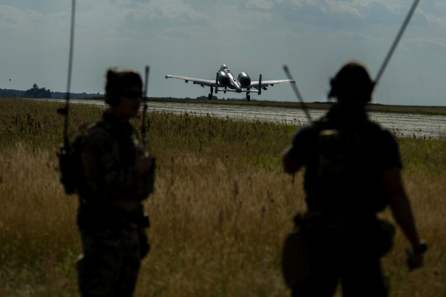 A 354th Expeditionary Fighter Squadron A-10C Thunderbolt II aircraft takes off in front of two 321st Special Tactics Squadron combat controllers during an austere landing training exercise at Nowe Miasto, Poland, July 20, 2015. The 321st STS combat controllers ground air traffic control for the A-10 pilots during the exercise. (U.S. Air Force photo by Airman 1st Class Luke Kitterman/Released)