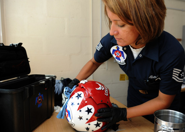 Tech. Sgt. Amber Alumpe, an aircrew flight equipment specialist, wipes down a Thunderbird helmet during post-flight inspections on the flight gear at Royal Air Force Base Waddington, United Kingdom, June 30, 2011. The Thunderbirds will perform in nine countries during their six-week European tour, fostering international goodwill and representing America's Airmen around the globe. (U.S. Air Force photo/Staff Sgt. Larry E. Reid Jr., Released)