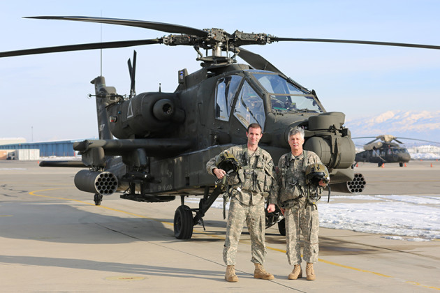CW5 Ken Jones poses with his son, CW4 Jared Jones, pose in front of the Boeing AH-64 Apache. Both men fly the helicopter. (Photo courtesy of Army National Guard)