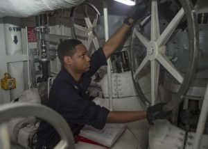 Engineman 2nd Class Cory Winston adjusts steam configurations in the catapult number two piping space of the aircraft carrier USS Dwight D. Eisenhower (CVN 69) (U.S. Navy photo by Mass Communication Specialist Seaman Apprentice Joshua Murray)