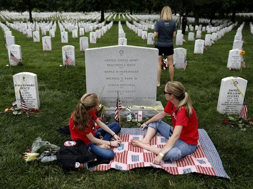 Leslie Hufstedler-Alverez and her daughter Grace Hufstedler sit at the grave of Lt Doyle Hufstedler at Arlington National Cemetery