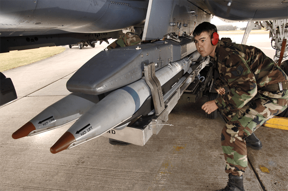 Staff Sgt. Randy Broome signals a jammer operator to move a Bomb Rack Unit 61 forward, while loading it onto an F-15E Strike Eagle at Royal Air Force Lakenheath, England
