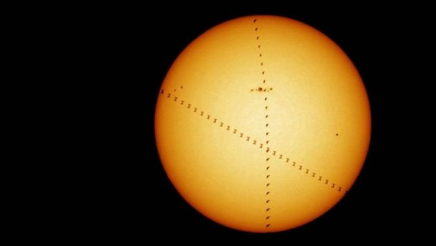 A bird (flying up the center of the image) crosses the face of the sun at the same time as the International Space Station