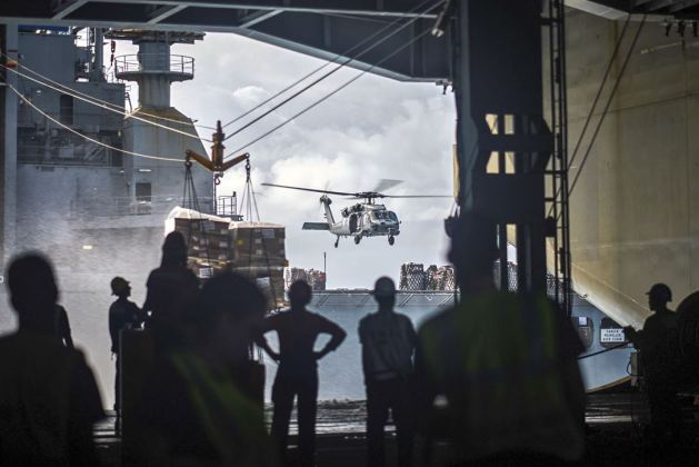 MH-60S Seahawk helicopter hovers over the dry cargo and ammunition ship USNS Charles Drew