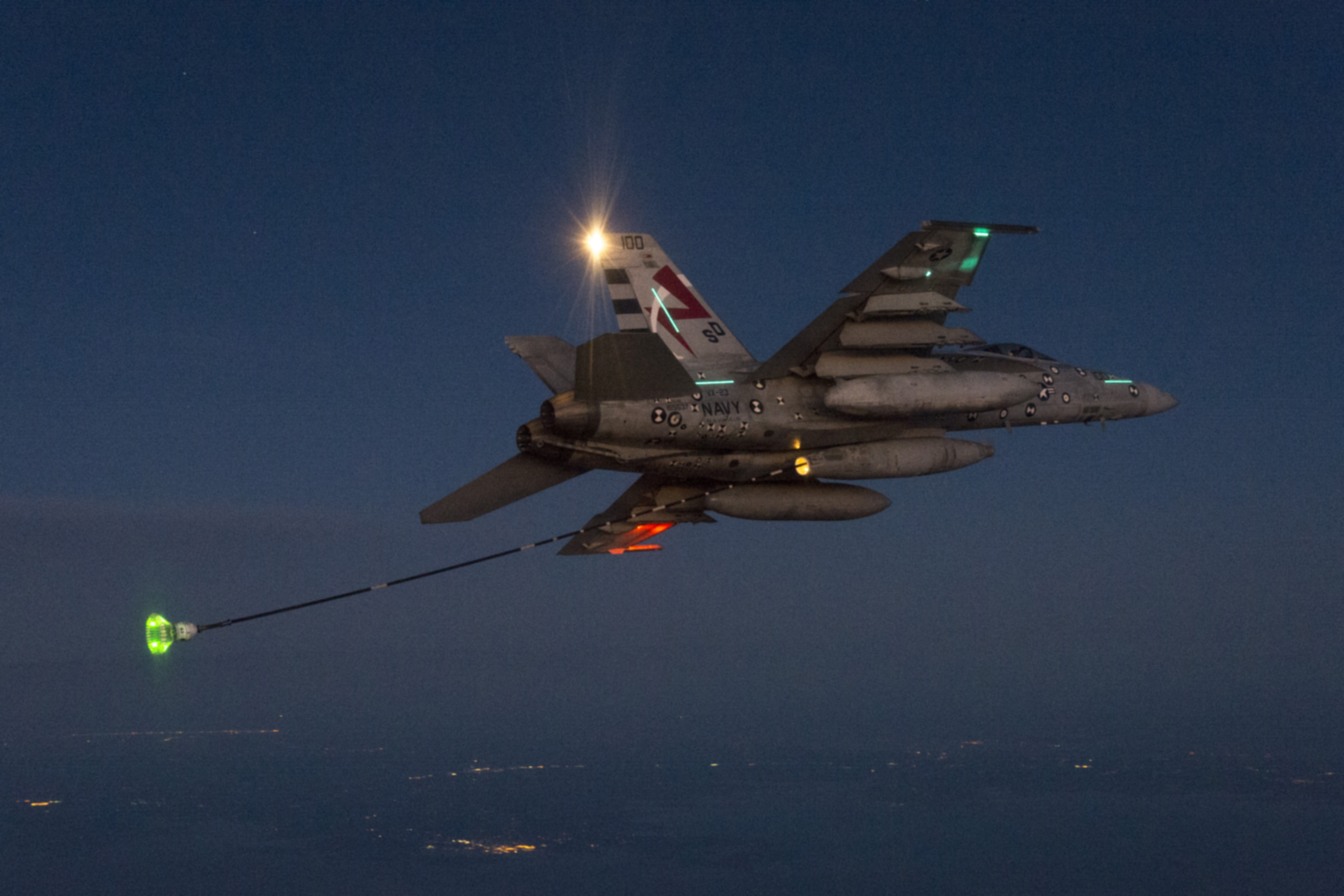U.S. Navy F/A-18E Salty Dog 100 of Air Test and Evaluation Squadron Two Three (VX-23) conduct night-time ARS ADV (Aerial Refueling Store Air Defense Variant) Low FOD Drogue Evaluation over the Chesapeake Bay on 14 Jan. 2016. VX-23 is part of Naval Test