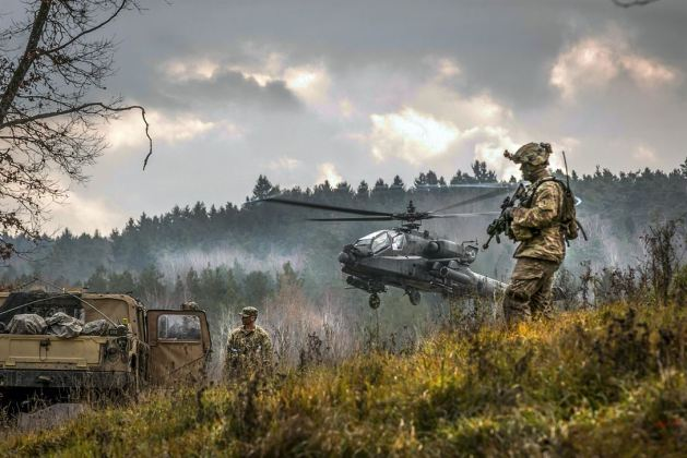 AH-64 Apache helicopter takes off near soldiers participating in the Allied Spirit VII training exercise in Grafenwoehr, Germany