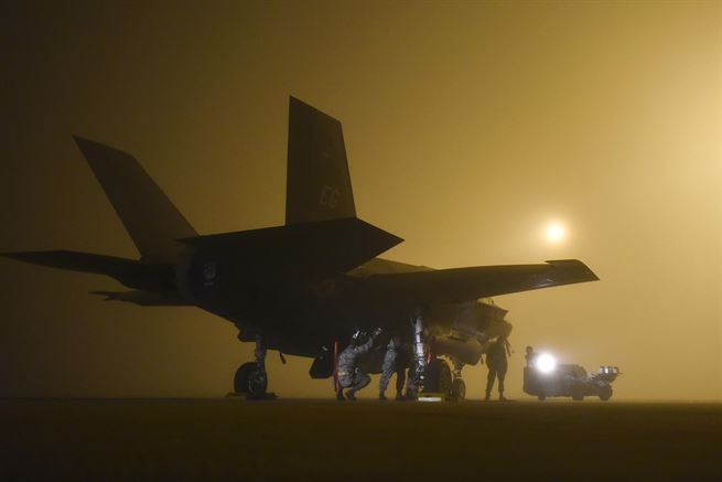 Air Force weapons crew loads a live GBU-12, a guided laser bomb, into an F-35A at Eglin Air Force Base