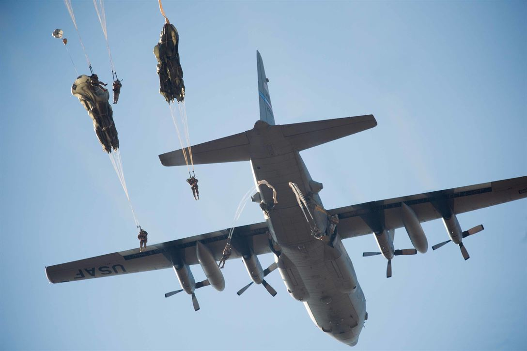Army paratroopers exit from a C-130 Hercules aircraft during an airborne operation for the 18th Annual Randy Oler Memorial Operation Toy Drop
