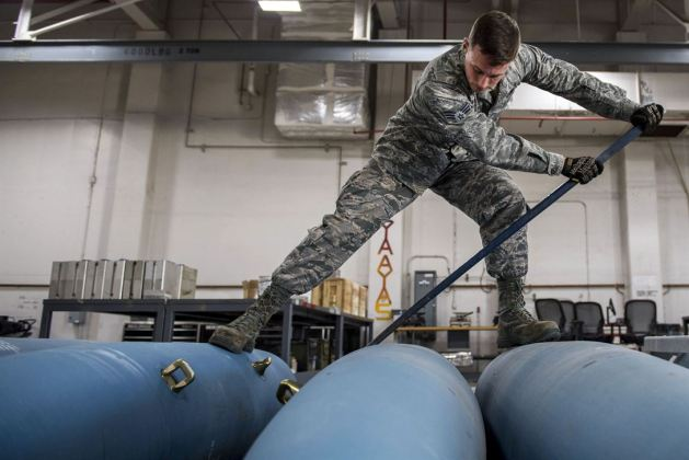 Air Force Senior Airman William Lawrence rolls over a bomb body at Barksdale Air Force Base