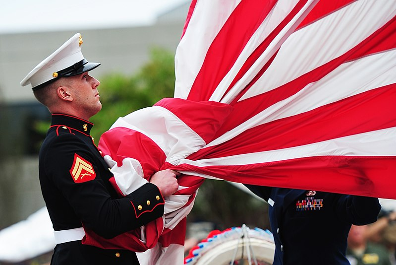 United States Marine takes the American flag into his hands