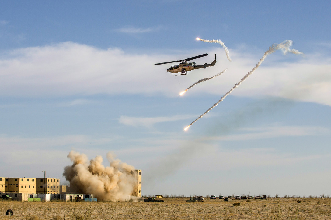 Marine Corps AH-1W Super Cobra helicopter deploys flares and launches rockets at mock enemy targets during a tactical demonstration at the Yodaville training facility in Yuma, Ariz