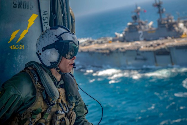 Navy Petty Officer 2nd Class Eric Smith rides in an MH-60S Seahawk helicopter
