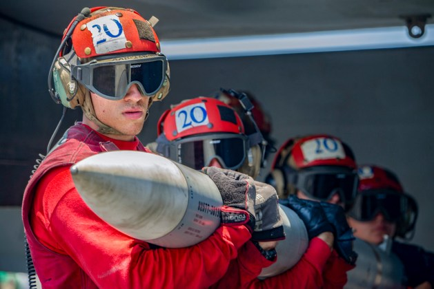 Petty Officer 3rd Class Zachary Andrew helps carry ordnance on the USS Harry S. Truman