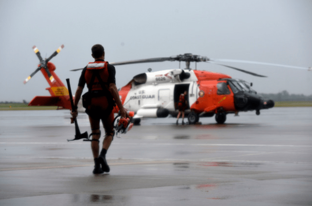U.S. Coast Guard rescue swimmer walks toward an MH-60 Jayhawk helicopter at Air Station Houston