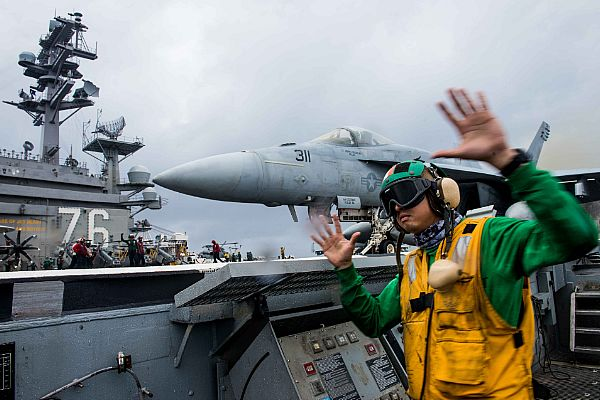Aviation Boatswain's Mate 1st Class Clayton Hudson Signals for Launch of an F/A-18E Super Hornet