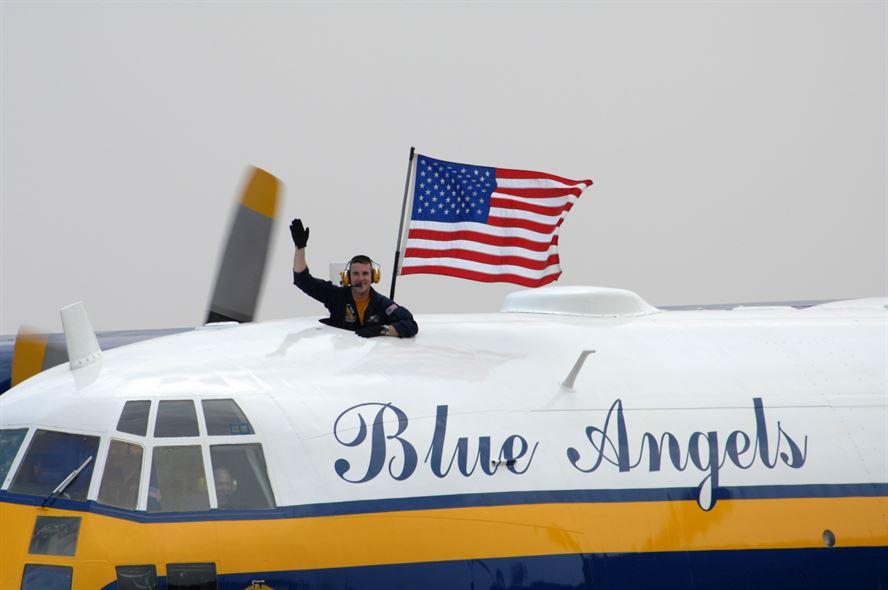 Blue Angels Fat Albert team carries an American flag