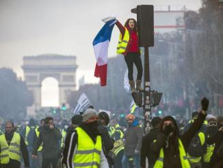 A woman wearing a yellow vest, as a symbol of French driver's and citizen's protest against higher fuel prices, waves a French flag during clashes with police.