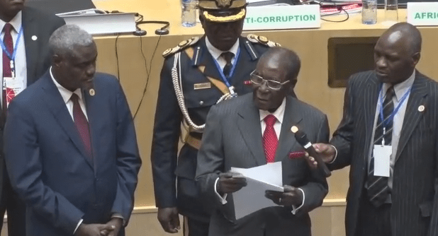 Zimbabwe President Robert Mugabe presents fundraising check of $1 million to the AU Summit