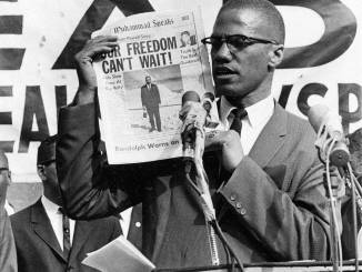 Malcolm X with Muhammad Speaks-AP