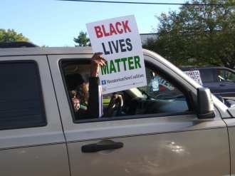 March against racist attacks in Warren where vehicle flashes BLM sign