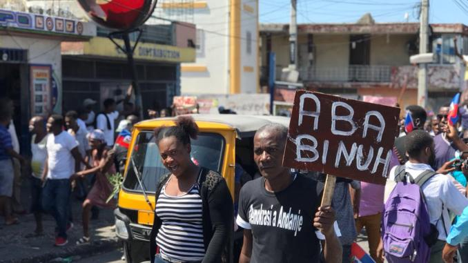 "Translation of protestor's sign: ""Down with BINUH"". BiNUH is the acronym for the changed name of the 17-year UN occupation ""United Nations Integrated Office in Haiti"""