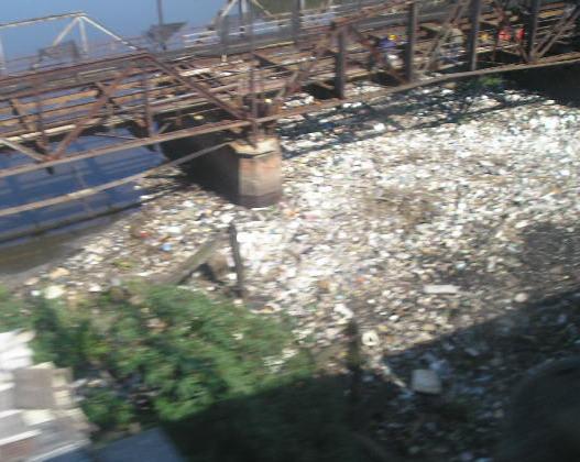 Mugre en el Riachuelo, que va a parar al Río de la Plata. Algo se evita con mangueras flotantes, pero desborda aun con poco, y ¡sigue contaminando! ¿Qué inspectores no lo ven? Fotos de FILATINA.