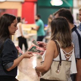 Jovem adventista explica conteúdo da revista para casal. Público recebeu bem a iniciativa (foto: Rodrigo Gorski)