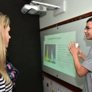 Sheila Oliveira acompanha apresenta de aluno durante Feira das Nações. Foto: Arquivo Pessoal/Sheila Oliveira
