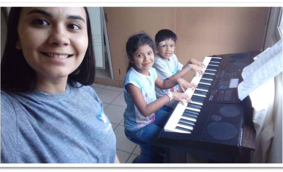 Voluntária ensina música para crianças da comunidade (Foto: Divulgação)