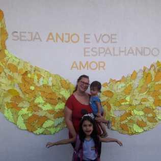 Rebeca Nunes com a mãe e o irmão posam para foto nas asas amarelas.