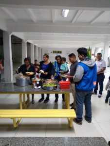 Voluntários serviram refeição aos imigrantes.[Foto: Divulgação].