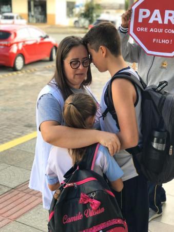 Mãe ora com seus filhos antes do início da aula.[Foto: Colégio Adventista]
