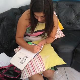 Voluntário escreve dedicatória em livro para entregar aos profissionais de saúde.[Foto: Reprodução].