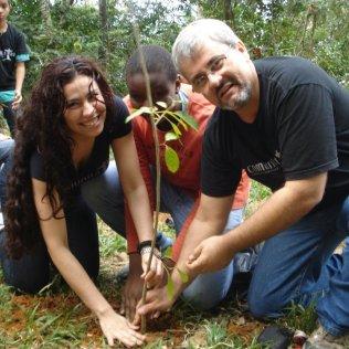Gabriela e Harrison plantando mudas com alunos do projeto. (Foto tirada antes da pandemia)
