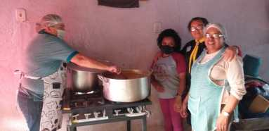 Voluntários preparam refeições para doação. [Foto: Reprodução].