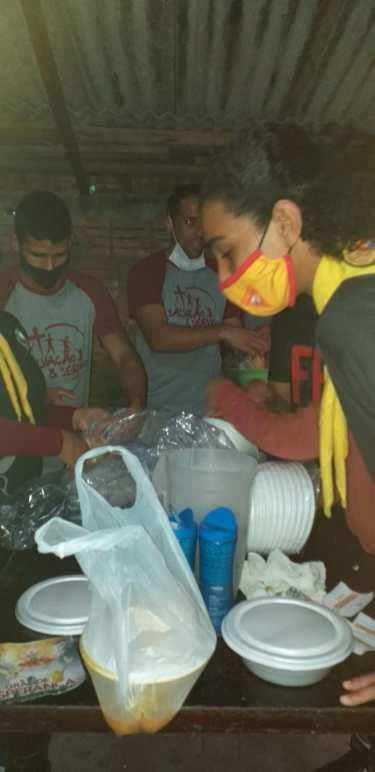 Grupo de voluntários durante preparação das marmitas. [Foto: Reprodução].