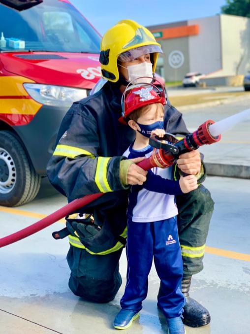 Bombeiro ensina aluno como manusear mangueira para combate a incêndios. [Foto: Reprodução].