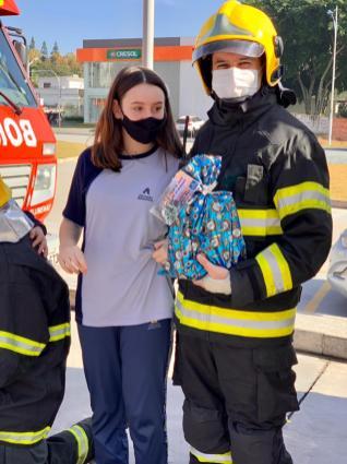 Bombeiros recebem presentes dos alunos do colégio. [Foto: Reprodução].