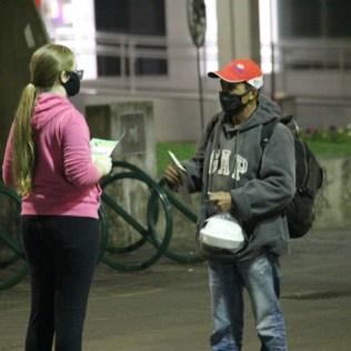 Aluna entrega kit de café da manhã e conversa com morador de rua. [Foto: Paulo Ribeiro].