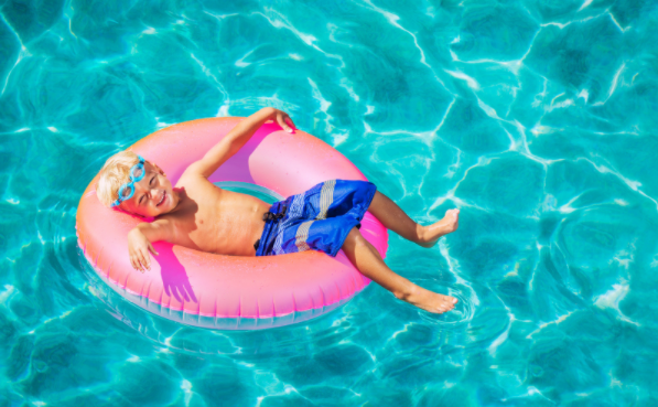 boy floating on inner tube in pool