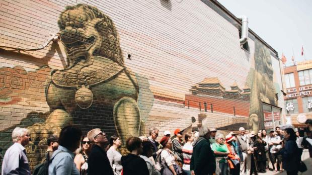 Group stands in alleyway in front of dragon mural listening to tour leader speak.