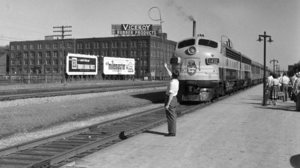 Black and white photo of a man in 50s clothing standing on a train platform waving at the approaching train. In the background is a building with a large sign that reads Viceroy rubber products.