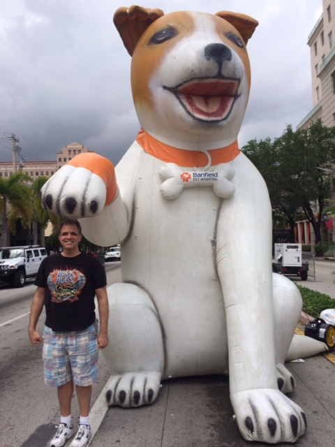 Matt standing next to a giant blow up dog with the dog's paw touching Matt's head.
