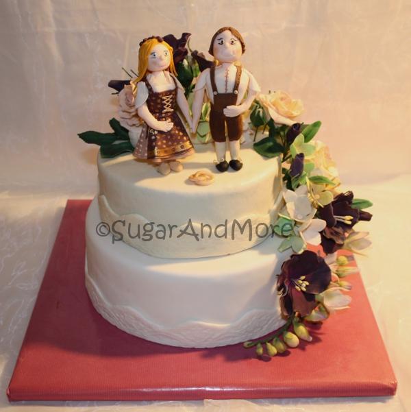 Hochzeitstorte mit Trachtenpaar und Bltenwasserfall