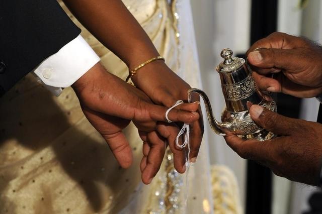 Un prêtre bénit un mariage au Sri Lanka en versant de l'eau sacrée afin de célébrer leur union.