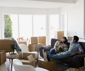 Couple with a child sitting on a couch getting set to unpack in their new home.